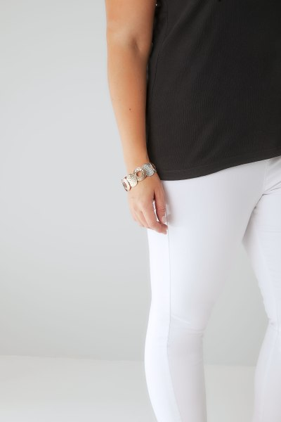 White jeans and metallic bracelet